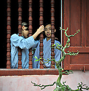 Two young Vietnamese monks chat by an open window in Thien Mu pagoda, Hue, Vietnam, Southeast Asia