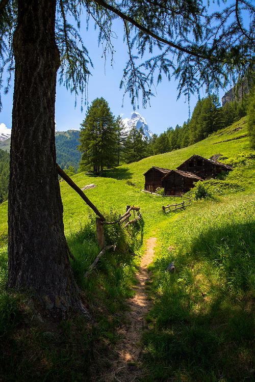 Walking trail passes chalet barns below the Matterhorn mountain in the Swiss Alps near Zermatt, Switzerland