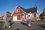 Kentaro och Maki Tago tillsammans med sina barn Rintaro, Sakura och Haruka, utanför sitt faluröda hus med triangelformat tak. Sweden Hills, Japan