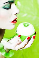 beautiful caucasian woman portrait show a peeled apple studio on green background