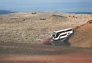 Tour bus in colcanic landscape Parque Nacional de Timanfaya, national park, Lanzarote, Canary Islands, Spain