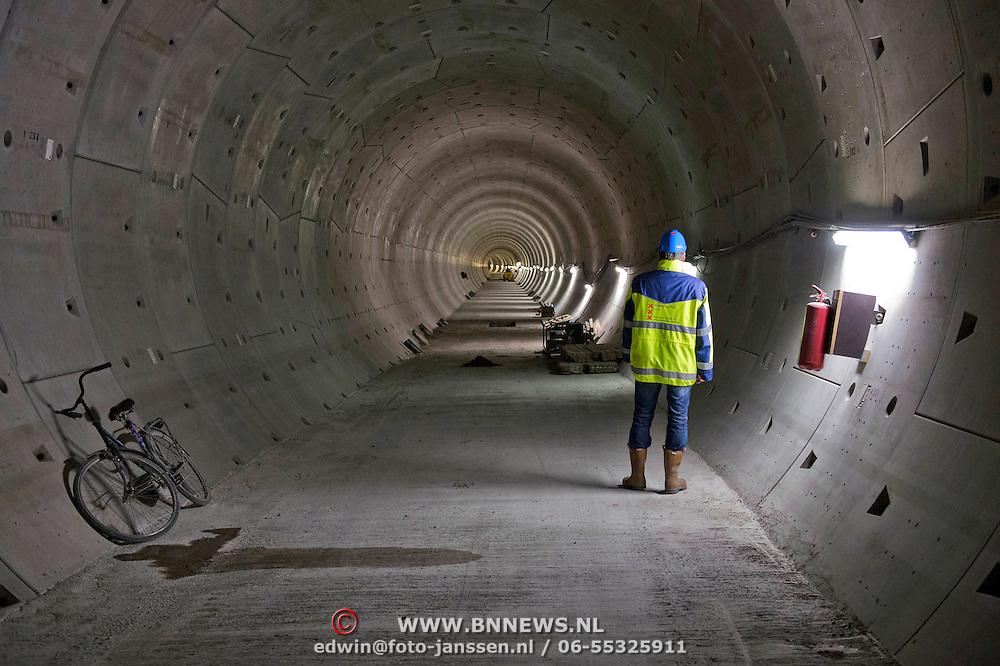 Een medewerker van de Noord Zuidlijn op weg naar de Paver die inmiddels in de tunnel onder het Rokin bezig is.