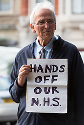 © Licensed to London News Pictures. 08/10/2013. London, UK. A man demonstrates outside the London Hospital in East London against the implementation of the Private Finance Initiative (PFI) debt within the Barts Health Trust group of hospitals in East London, which includes St Bartholomew's, The Royal London, Newham General, Whipps Cross and The London Chest. Photo credit : Vickie Flores/LNP