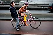 Een meisje fietst met een jongen achterop de Erasmusbrug in Rotterdam omhoog