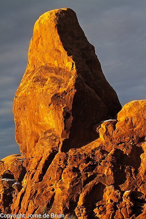 A close up of Turret Arch bathing in sunset light in Arches National Park, Utah.