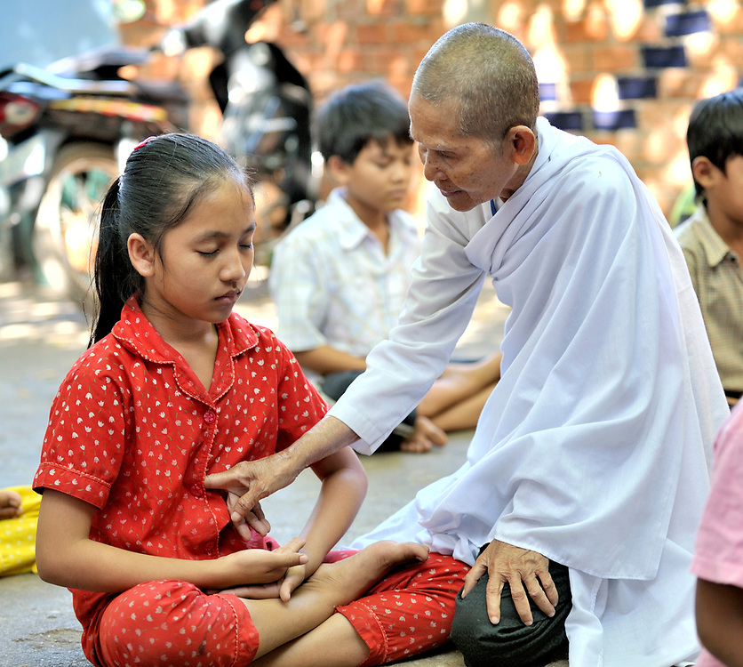Buddhist nun Mao Phorn helps students--mostly orphans and other vulnerable children, many of them infected or affected by HIV and AIDS--to engage in mediation before their morning class at a school in the Beungkak neighborhood of Phnom Penh which is run by the Salvation Centre Cambodia, an organization that works with Buddhist monks and other activists to do education and advocacy and care for people infected or affected by HIV and AIDS.