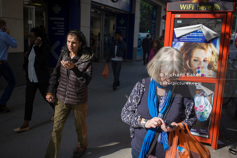 A woman texts a friend in front of a red phone kiosk advertising Natwest's online banking for students.