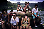 "Sailors from the cargo vessel Aranui loading and sitting on ""Copra"", dried coconut shells, Ua Huka Island, French Polynesia."