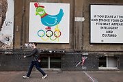 Olympic birdz graffiti by artist Ronzo. This subversive street art painting near Brick Lane in East London, UK, shows a pigeon defecating on the Olympic rings.