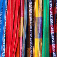 South America, Ecuador, Otavalo. Textiles. cloths, blankets, scarves, and hammocks hang on display at the Otavalo Market.