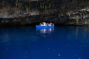 Tourists take a rowing boat trip around Melissani Lake near Sami, Kefalonia, Greece. Kefalonia is an island in the Ionian Sea, west of mainland Greece.