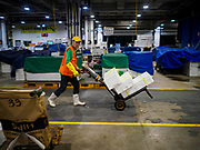 06 JUNE 2018 - SEOUL, SOUTH KOREA: A porter pushes boxes of fresh frozen fish through the Noryangjin Fish Market. The Noryangjin Fish Market is the largest fish market in Seoul and has been in operation since 1927. It opened in the current location in 1971 and was renovated in 2015. The market serves both retail and wholesale customers and has become a tourist attraction in recent years.       PHOTO BY JACK KURTZ