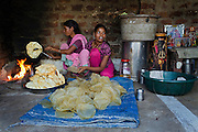 Poonam, 12, (right) is learning to cook Papard (a cheaply-made, fried rice snack) with her mother Sangita, 41, while sitting in the kitchen / temple area of their newly built home in Oriya Basti, one of the water-contaminated colonies in Bhopal, central India, near the abandoned Union Carbide (now DOW Chemical) industrial complex, site of the infamous '1984 Gas Disaster'.