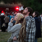 Young couple look at the moon coming through while they listen to live music at the Super Normal art and music festival.