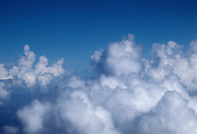 Looking down on cumulous clouds from above with blue sky.