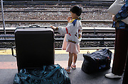 a little girl waiting with her parents for the train
