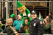 A New York Department of Correctiosn officers poses with a large stuffed leprechaun.