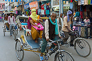 Street scene in holy city of Varanasi, young muslim woman in coloured burkha rides in rickshaw, Benares, Northern India