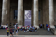Tourist visitors sit beneath and walk past the columns of London's British Museum. Above them and between pillars is a giant poster called Head of a Woman (1470s) by Andrea del Verrocchio born Andrea di Michele di Francesco de' Cioni, an Italian sculptor, goldsmith  and painter who worked at the court of Lorenzo de' Medici in Florence. His pupils included Leonardo da Vinci, Pietro Perugino and Lorenzo di Credi, but he also influenced Michelangelo. The British Museum's collection of Italian Renaissance drawings is so fragile that its masterpieces are exhibited only once in a generation. About half of the works came from Florence in partnership with the Uffizi and sponsored by BP (British Petroleum). The 100 or so works span the period 1400-1510 by artists including Jacopo and Gentile Bellini, Botticelli, Filippo Lippi, Mantegna, Michelangelo and Raphael.