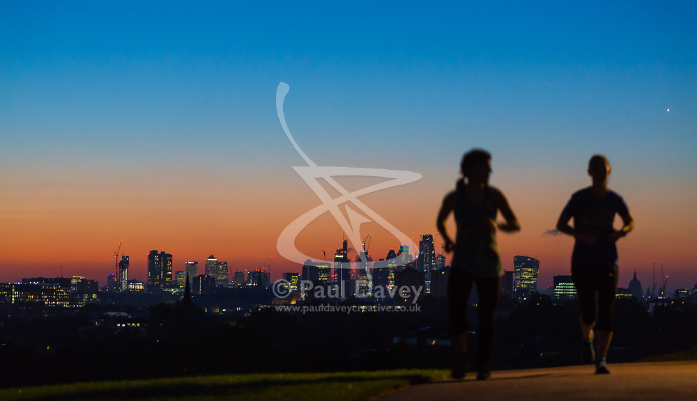 London, October 27 2017. Runners in silhouette against the pre-dawn sky as the day breaks over London's skyline, seen from Primrose Hill. © Paul Davey