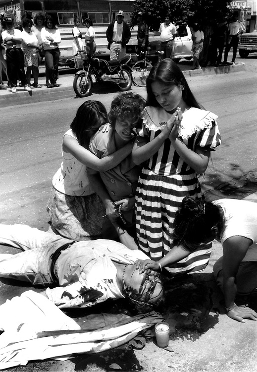 Murder victim surrounded by his grieving family. Oaxaca Mexico