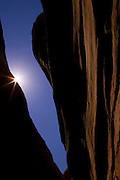 The midday sun shines through a narrow opening at the top of a slot canyon in the Coyote Gulch area of the Grand Staircase Escalante in Utah.
