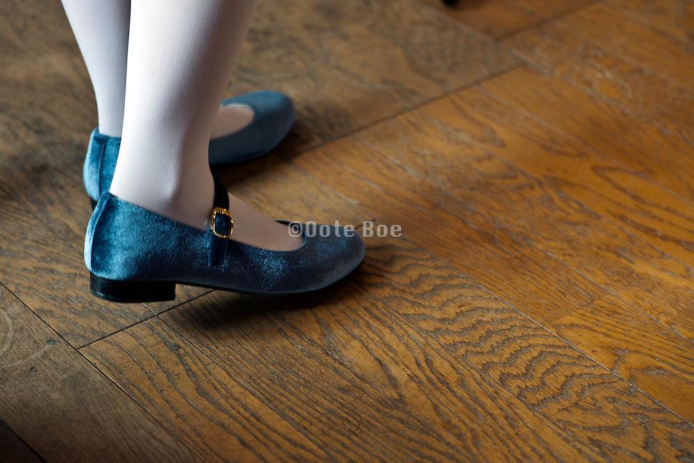 girl walking on wooden floor in blue shoes