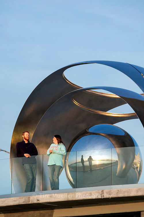Baton Rouge visitors Matthew Mueller and Addison Stults enjoy a view of the Mississippi river from the deck of the Rotary Club's 14-foot-tall stainless-steel sculpture created by California-based and Hong Kong-born visual artist Po Shu Wang. The sculpture consists of three stainless steel reflective spheres nestled within each other.