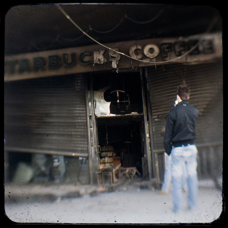 The burned Starbucks in Aeolou street, Omonia, Athens. <br /> <br /> Following the murder of a 15 year old boy, Alexandros Grigoropoulos, by a policeman on 6 December 2008 widespread riots, protests and unrest followed lasting for several weeks and spreading beyond the capital and even overseas<br /> <br /> When I walked in the streets of my town the day after the riots I instantly forgot the image I had about Athens, that of a bustling, peaceful, energetic metropolis and in my mind came the old photographs from WWII, the civil war and the students uprising against the dictatorship. <br /> <br /> Thus I decided not to turn my digital camera straight to the destroyed buildings but to photograph through an old camera that worked as a filter, a barrier between me and the city.