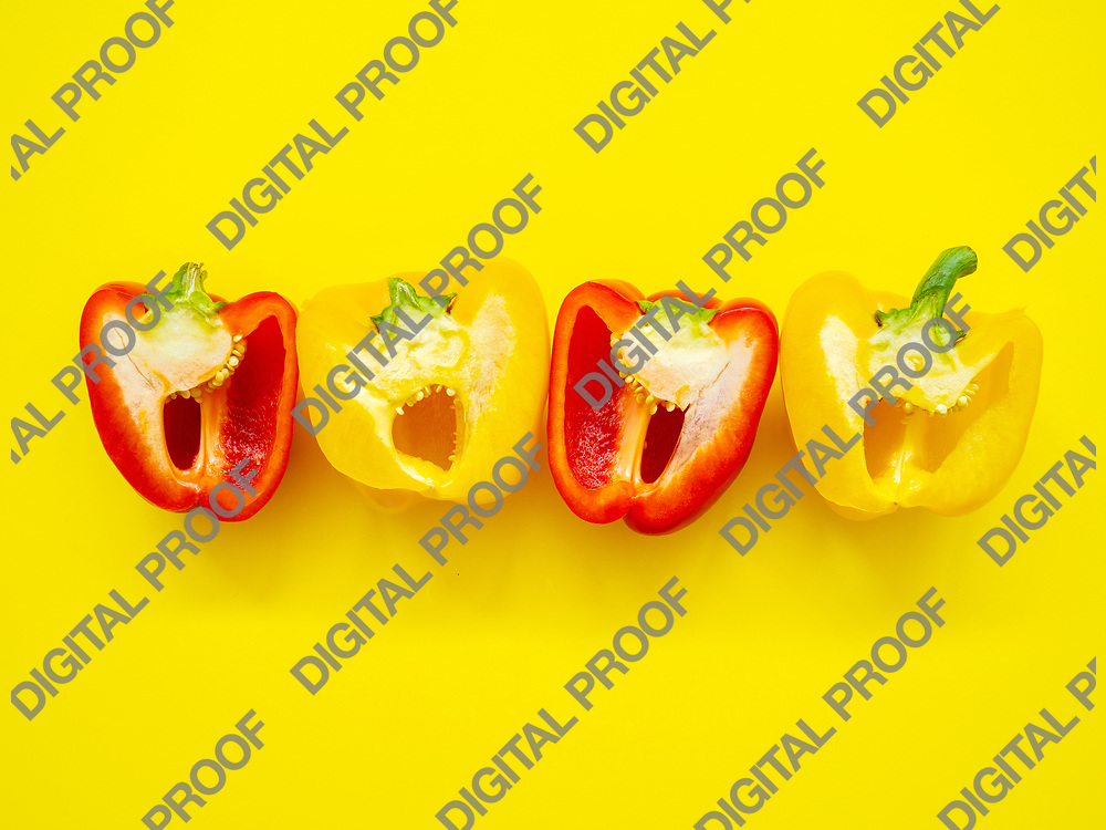 Red and yellow bell peppers sliced by the half with seeds isolated in yellow background viewed from above - flaylay concept