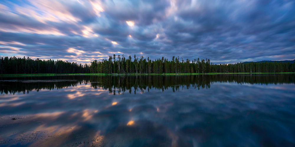 A full moon lights the clouds on fire as they reflect in the calm waters of a lake in Harriman State Park in Idaho.