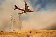HEALDSBURG, CA - OCTOBER 26: An air tanker flies over PG&E power lines en route to drop fire retardant in the valley below during the firefighting operations to battle the Kincade Fire in Healdsburg, California on October 26, 2019. (Photo by Philip Pacheco/AFP)