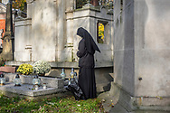 A nun remembers her deceased loved ones at Rakowicki Cemetery in Krakow, Poland 2019.
