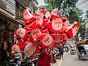23 DECEMBER 2017 - HANOI, VIETNAM: A woman sells inflatable Santa Claus toys in the old quarter of Hanoi. The commercial and gift giving aspect of Christmas is widely celebrated in Vietnam. Vietnam's 5+ million Catholics also celebrate the religious aspects of Christmas.       PHOTO BY JACK KURTZ