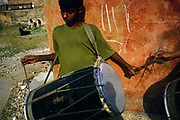 A boy practices his tabla drum in the street, Shadipur Depot<br /> The Kathiputli Colony in the Shadipur Depot slum is home to hundreds of (originally Rajasthani) performers. The artistes who live here - from magicians, acrobats, musicians, dancers and puppeteers are often international renowed by always return to the Shadipur slum.
