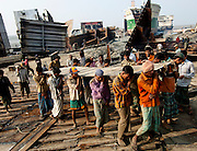 Men with no safety gear carry steel plates cut from broken ships in a ship breaking yard in Chittagong, Bangladesh, on the 12th December 2006.<br />