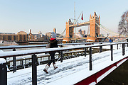 A woman wearing a bobble hat walks across a snow covered bridge in front of Tower Bridge in London, England on February 28th, 2018. Freezing weather conditions dubbed the Beast from the East have brought snow and sub-zero temperatures to the UK.