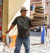 A man sells a stack of hats on the street in Huaraz, in the Santa Valley (Callejon de Huaylas), Ancash Region, Peru, Andes Mountains, South America.
