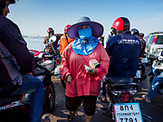 22 JANUARY 2019 - PHRA PRADAENG, SAMUT PRAKAN, THAILAND:  The ticket seller collects fares on a motorcycle and vehicle ferry that crosses the Chao Phraya River in Phra Pradaeng, in the suburbs south of Bangkok. The use of vehicle ferries across the river has gone down as the government has built bridges to connect communities on both sides of the river. The Phra Pradaeng ferries are the busiest vehicle ferries in the Bangkok metropolitan area. Since the BTS Skytrain now comes close to the ferry, the number of commuters going into Bangkok that use the ferry has increased.     PHOTO BY JACK KURTZ