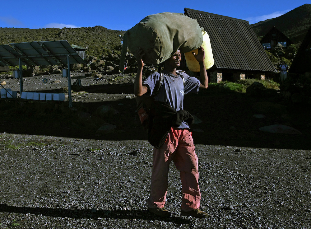 A porter prepares to head out in the early morning light for the trail up Mt. Kilimanjaro. The porters carry the bulk of the food and supplies for the climbers and make the trip up the mountain about once or twice a month.