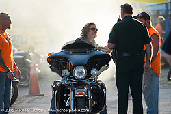 Stopped in his tracks. A policeman shuts down a great burnout at the Iron Horse Saloon during Daytona Beach Bike Week. Ormond Beach, FL, USA. Sunday March 8, 2015.  Photography ©2015 Michael Lichter.