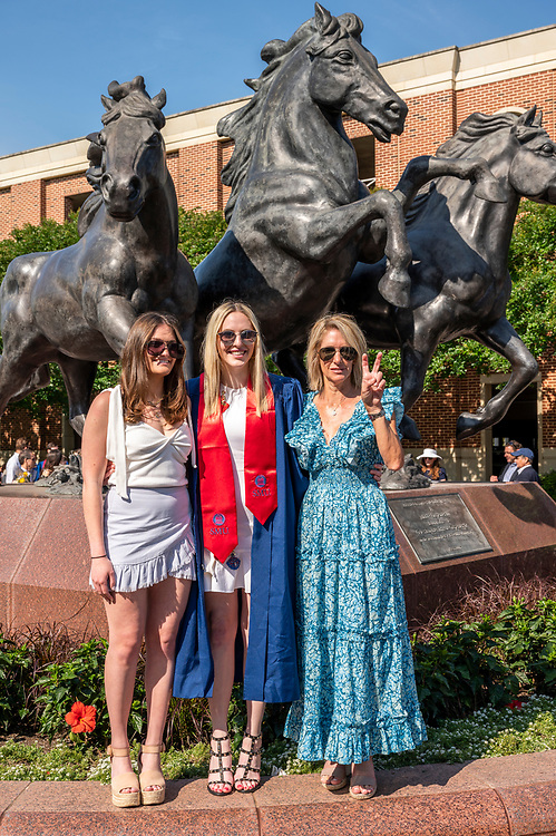 New graduates and their families pose for pictures following the May Commencement Ceremony at Mustang Plaza and Mall, Saturday, May 15, 2021 on the SMU Campus.