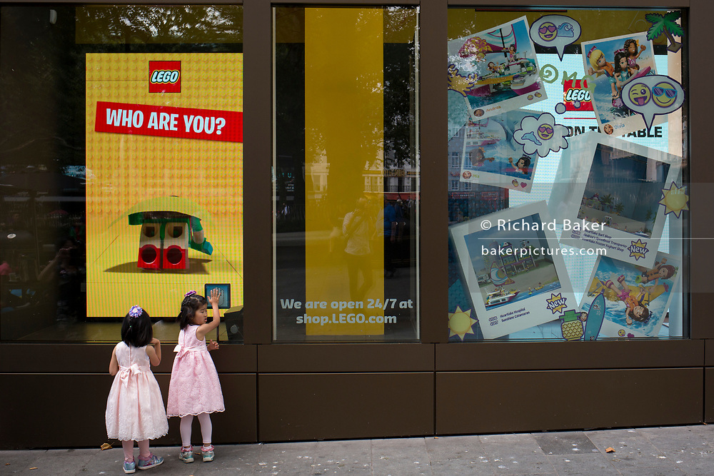 Two young girls in matching pink dresses look into the Lego window, on 31st July 2017, in Leicester Square, London, England.