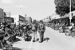"""Property of Paul. Main Street, Sturgis, SD, 1979<br /> <br /> Limited Edition Print from an edition of 50. Photo ©1979 Michael Lichter<br /> <br /> Description: When I first got my """"Property Of"""" buckle, I hated it.  I wasn't going to wear it so it hung on the back of my chair for 3 weeks. I got the impression that this guy thought he owned me and controlled me but I knew I was a single, independent woman and I wasn't anybody's property.  My man wasn't happy. I didn't understand that it meant more to him to give me that Buckle than to give me a diamond ring. <br /> <br /> Eventually, I started getting to know more people and realized that if you wore the buckle, you were more respected by the brothers in the club.  It also provides protection, to a certain degree, because people realize you are with a club and they leave you alone.<br /> <br /> I have been wearing my buckle for almost six years now. I feel naked without it.  It's a part of me and I wear it with pride.  <br /> <br /> Donna on """"Property,"""" 2003"""