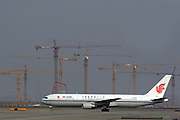 An Air China plane arrives at Beijing's Shoudu International Airport on a runway next to the construction site of a new airport in Beijing March 20, 2005.
