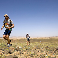25 March 2007: Runner #403 Mario Malerba of Italia runs across a blooming desert because of a rainy winter between Irhs and Khermou during the first stage of  the 22nd Marathon des Sables, a 6 days and 151 miles endurance race with food self sufficiency across the Sahara Desert in Morocco. Each participant must carry his, or her, own backpack containing food, sleeping gear and other material.