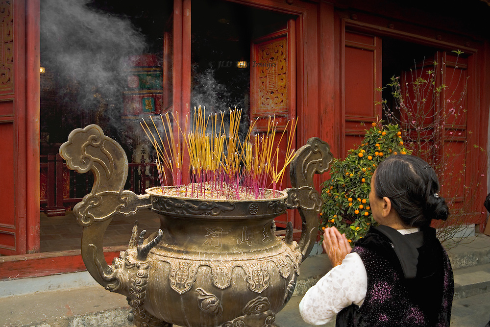 Woman praying, palms together and raised before a cauldron of burning joss sticks, at the  Ngoc Son Pagoda, Hanoi, North Vietnam.  Smoke from the incense wafts toward the open door of the pagoda.