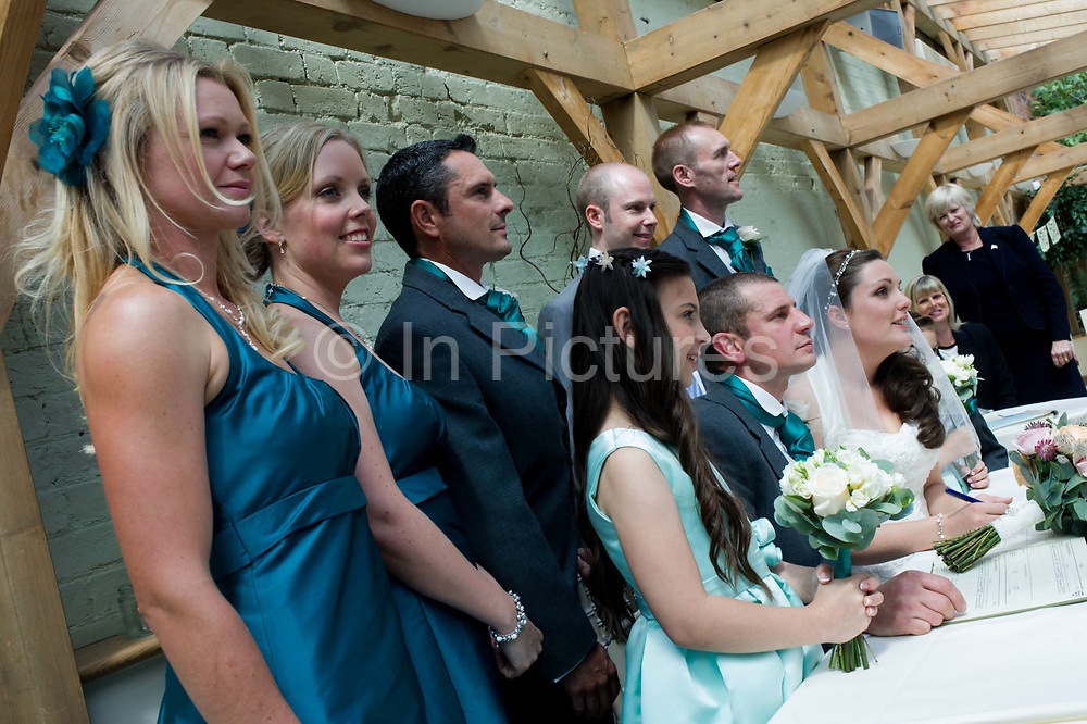 Bride, groom with bridesmaids and ushers have formal portraits taken after a civil ceremony in Essex, England. Dressed in matching turquoise blue as decided by the bride this European wedding has taken place inside a covered Orangery at a private wedding and event venue. Rather than marrying in a religious context, the happy couple have preferred to tie the knot in this popular setting for a non-church meaning.