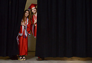Scarlett Davalos and Mazie Pini peek out from behind a curtain looking for family before the start of the Mundelein High School graduation on Sunday, May 17 at the Sears Centre in Hoffman Estates.