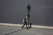Man crosses the line of a lamp post shadow against a grey construction hoarding in central London's Trafalgar Square.